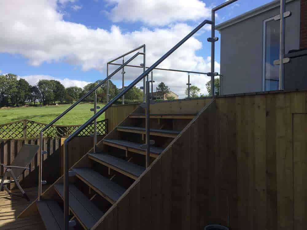 Stainless steel handrails installed around deck and staircase